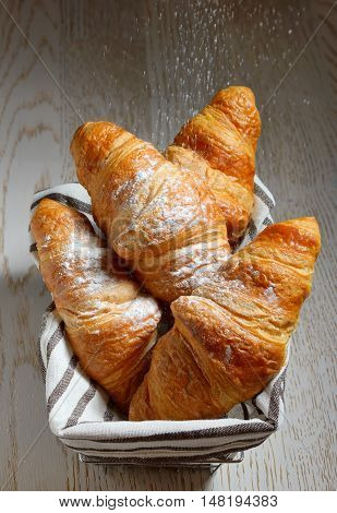 Tasty croissants in basket on wooden background