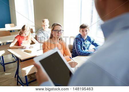 education, school, teaching, technology and people concept - group of happy students and teacher with tablet pc computer