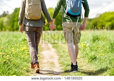 travel, hiking, backpacking, tourism and people concept - close up of happy couple with backpacks holding hands and walking along country road