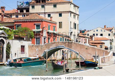 VENICE, ITALY - AUGUST 3, 2016: Tourists enjoying the gondolas in a canal. The gondolas are the most popular and romantic transportation in the city.
