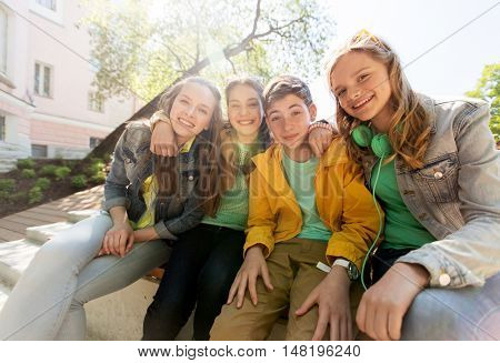 friendship and people concept - happy teenage friends or high school students hugging