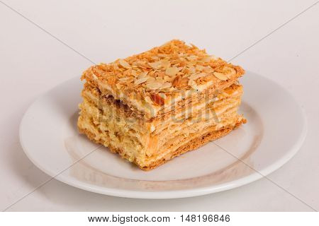 honey cake on a plate cut a piece isolated on white background for the menu