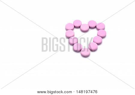 Heart shape of pink pills isolated on white background. Tablets of drug for asthma treatment.