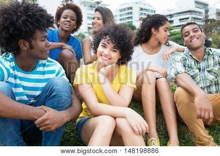 Group of happy latin caucasian and african american young adults outdoor in a park in the summer