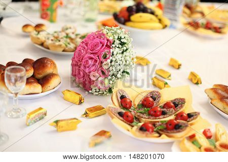 wedding bouquet on a banquet table with sandwiches as ladybirds