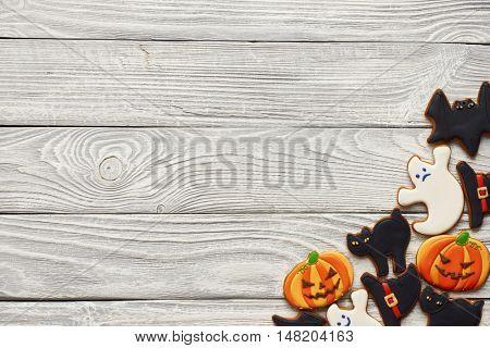 Halloween homemade gingerbread cookies over wooden background