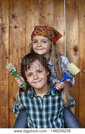 Kids ready to repaint wooden wall - holding brushes and smiling
