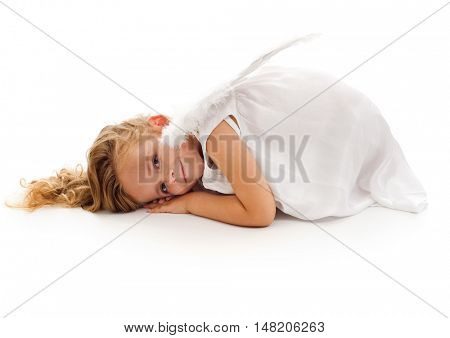 Little girl with angel wings resting on the floor in a curled up position - isolated
