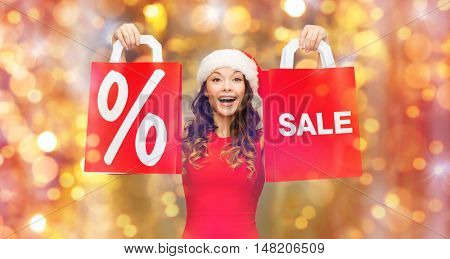 sale, christmas, holidays and people concept - happy smiling young woman in santa hat holding red shopping bags with percent sign over lights background