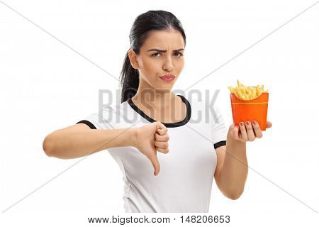 Young woman holding a bag of fries and making a thumb down gesture isolated on white background