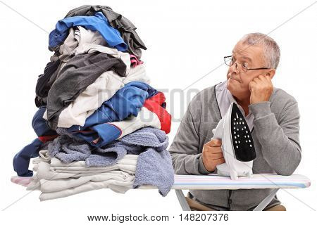 Sad elderly man holding an iron and looking at a pile of clothes isolated on white background