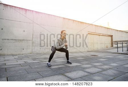 fitness, sport, exercising and healthy lifestyle concept - happy woman doing squats outdoors