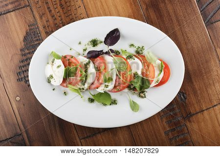Salad with Mozzarella cheese and tomatoes in white oval plate. wooden background.