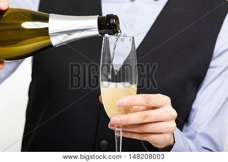 Waitress pouring wine in a glass
