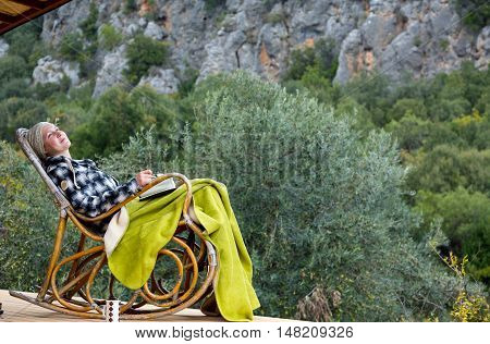 Woman relaxing on Vintage rocking Chair at Balcony of wooden rural Bungalow Forest and Mountains on background