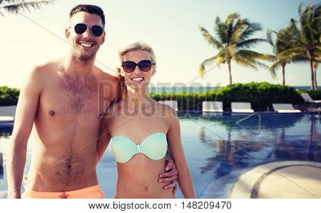love, travel, tourism, summer and people concept - smiling couple on vacation in swimwear and sunglasses hugging over hotel resort and swimming pool background