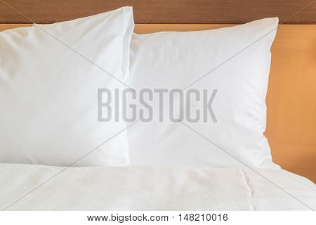 Clean white pillow on bed in hotel room