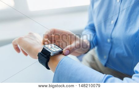 business, technology, online communication and people concept - close up of woman hands with messenger on smart watch screen at office