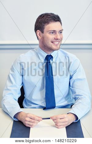 business, people and work concept - smiling businessman sitting in office in front of whiteboard