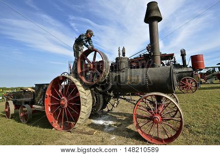 ROLLAG, MINNESOTA, Sept 1. 2016: An unidentified young lad works on an Advance Straw Burner vintage steam engine at the West Central Steam Threshers Reunion in Rollag, MN attended by 1000's held annually on Labor Day weekend.
