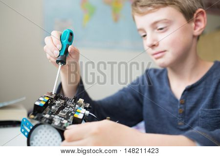 Young Boy Assembling Robotic Kit In Bedroom