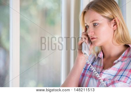 Anxious Young Woman Standing By Window Phoning Helpline