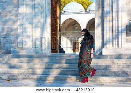 Islamic Style dressed eastern Woman walking on Marble stairs of Mosque outdoors