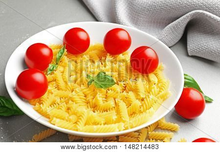 Plate with fusilli pasta and cherry tomatoes on table