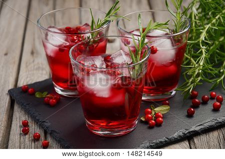 Refreshing drink with cranberries and rosemary on wooden background, selective focus