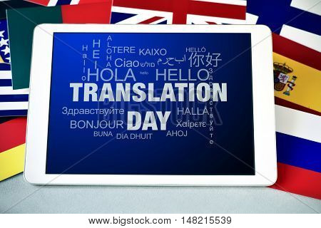 the text Translation Day in the screen of a tablet computer, and the word hello in different languages, surrounded by flags of different countries