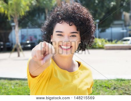 Caucasian girl with curly black hair pointing at camera outdoor in the city in the summer