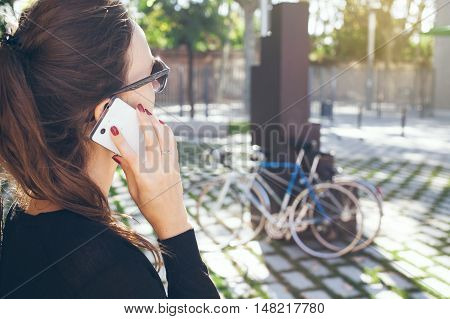 Beautiful female is speaking by smart phone in the park. Sun flare effect. Close-up of young female wearing hipster sunglasses who is having serious phone call, listening attentively. Work call