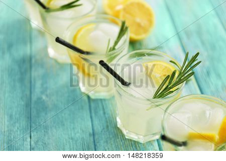 Cold fresh cocktails with lemon on wooden background