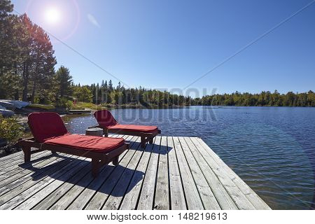 Wooden chairs overlooking a lake on a sunny day with lens flares