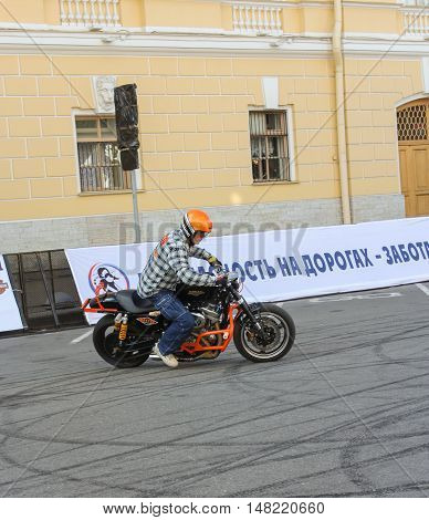 St. Petersburg, Russia - 12 August, Biker entering the turn with the skid,12 August, 2016. The annual International Festival of Motor Harley Davidson in St. Petersburg Ostrovsky Square.