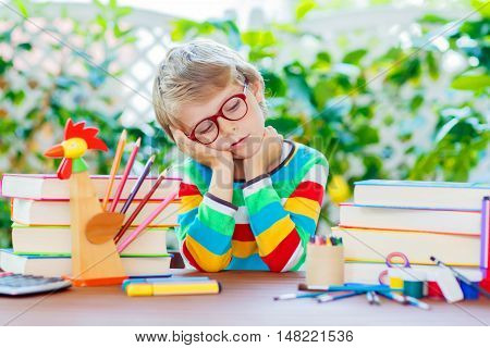 Frustrated sad little kid boy with glasses and lots of pupil's stuff like crayons pens, scissors and books. Tired child and student is back to school and happy about begin of lessons.