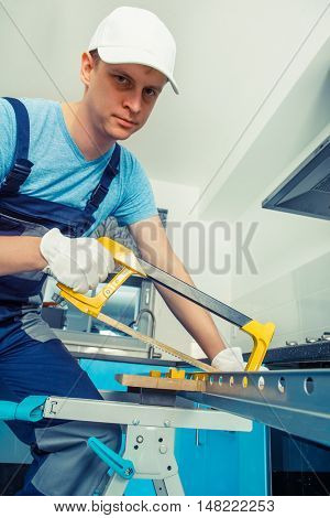 Handyman with cap and protective gloves on using a hacksaw to cut a steel plank