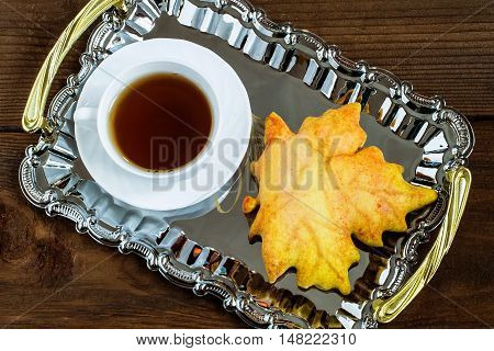 Homemade gingerbread cookie in the shape of a maple leaf and a cup of tea on a tray. It is served for breakfast or as a surprise gift