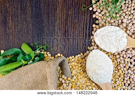 Chickpeas and chickpea flour in a spoon, green pods on burlap background on wooden board
