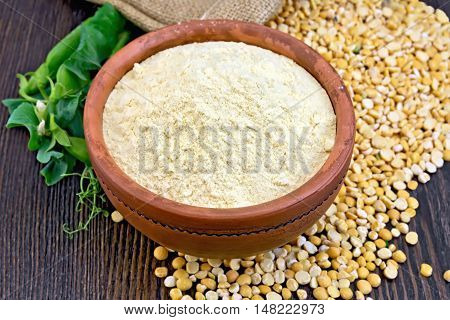 Flour pea in a clay bowl, flakes and fresh pods on a background of wooden boards