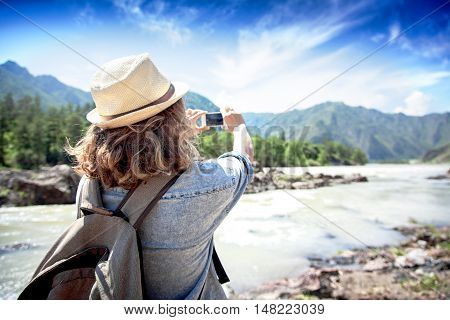 Young Woman Traveler On A Background Of Mountains Takes Photos On A Mobile Phone. Travel Concept.