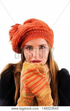 Concept of Beautiful Frozen Girl in Orange Striped Knitted Hat and Mittens Black Warm Sweater and Scarf isolated on White background