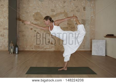Attraktive woman doing yoga exercise in a room
