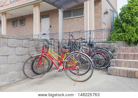 Many bicycle parked at bicycle parking space in front of home residential