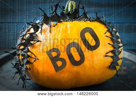 Idea homemade decorating for Halloween. Application: barbed tape made of black crepe paper and word boo on pumpkin. The original design in the style of Halloween. Tinted photo