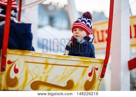 Adorable little kid boy on a carousel, ferris wheel at Christmas funfair or market, outdoors. Happy child having fun. Holiday, children, lifestyle concept.