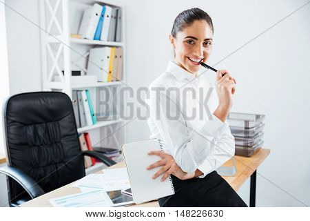 Charming young businesswoman sitting on the table at office and looking at camera