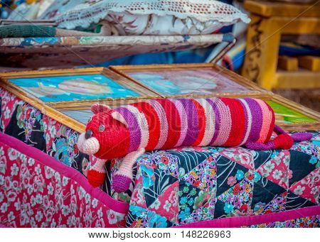 Zaporizhia/Ukraine- September  17, 2016: Family festival of homemade pickled canned vegetables and preserves. Exhibition - sale of handmade sewing and knitting products. Colorful knitted toy cat, patchwork blanket, pillow and paintings.