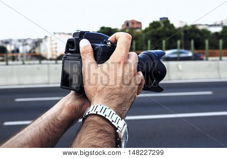 Man's hands holding photo camera near the road