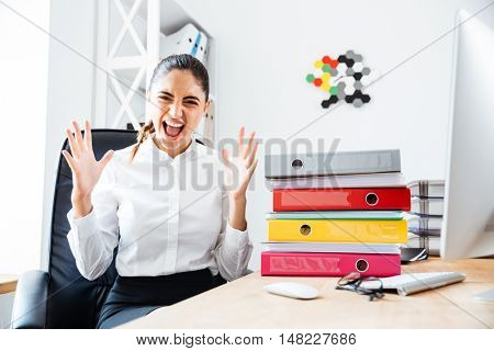 Angry crazy businesswoman screaming while sitting at workplace in office